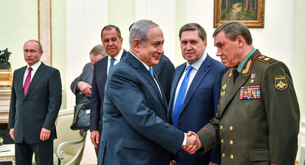 Israeli PM Netanyahu shakes hands with Russian Chief of the General Staff of the armed forces Gerasimov as Russian President Putin stands nearby during their meeting at the Kremlin in Moscow
