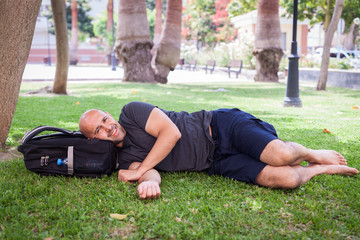 A young man is relaxing in a park under a tree with a backpack under his head