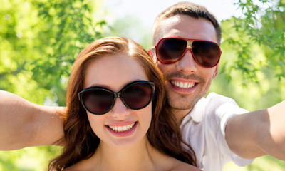 love, summer and people concept - smiling couple wearing sunglasses making selfie over green natural background