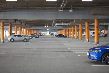 Underground parking is a large shopping center. There are not many cars. The image can be used as a background, there is room for text placement