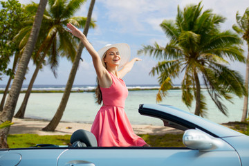 travel, summer holidays, road trip and people concept - happy young woman wearing hat in convertible car enjoying sun over tropical beach background in french polynesia