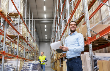 logistic business, shipment and people concept - happy businessman or manager with clipboard and loader at warehouse