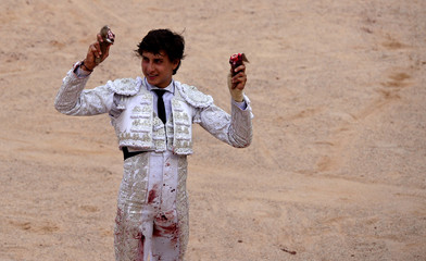 Peruvian bullfighter Andres Roca Rey holds up the ears of a bull won during a bullfight on the sixth day of the San Fermin festival in Pamplona