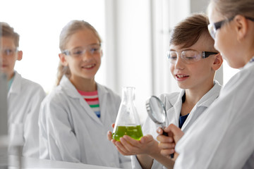 education, science and children concept - kids or students with test tube and magnifier studying chemistry at school laboratory