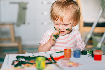 Portrait of adorable baby girl painting at home.