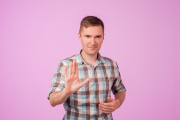 Portrait of european serious young man stretching hand towards camera with stop or hold gesture