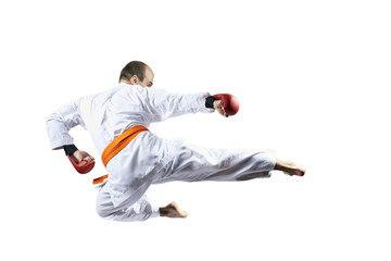 On a white background, an athlete beats a kick in a jump
