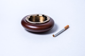 Stylish exquisite ashtray and cigarette on a white background