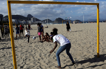 Nobel prize winner Malala Yousafzai plays a penalty kick during a meeting with teenage girls from Complexo da Penha who work with football organization Street Child United at Copacabana beach in Rio de Janeiro