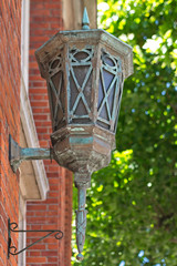 Close-up of Vintage Victorian Style Lantern on the Brick Wall Building with Trees in the Background