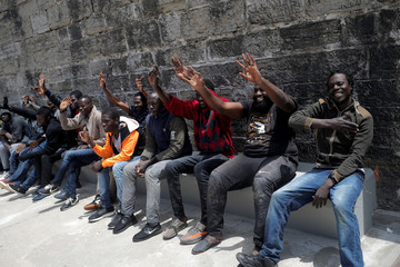 Migrants wave to their rescuers after arriving on a rescue boat at the port of Tarifa