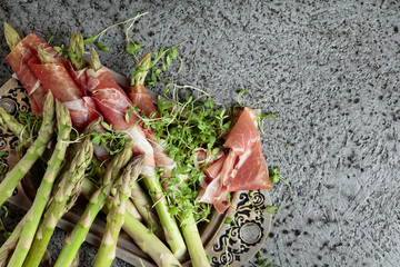 Asparagus wrapped in prosciutto with cress salad .