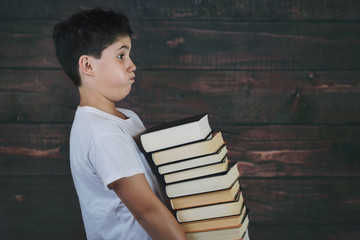 child with pile of books on wooden background