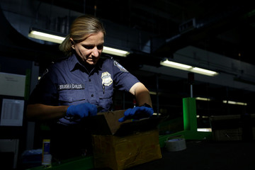 A U.S. Customs and Border Protection officer inspects a package arriving at the International Mail Facility at O'Hare International Airport in Chicago,