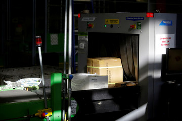 Packages on a conveyor belt are screened by an U.S. Customs and Border Protection officer as they arrive at the International Mail Facility at O'Hare International Airport in Chicago
