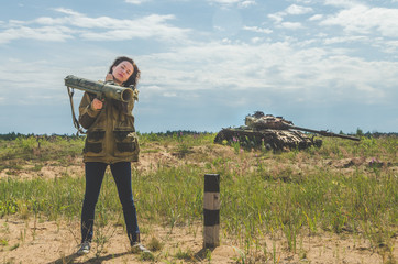 girl in military uniform and jeans with a Bazooka in her hands