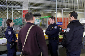 U.S. Customs and Border Protection officers talk at the International Mail Facility at O'Hare International Airport in Chicago
