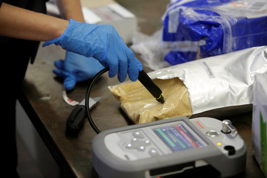 U.S. Customs and Border Protection officer Ella Olejnik uses an infrared machine to test a substance in a plastic bag in Chicago
