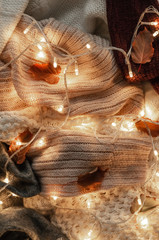 Background with warm sweaters. Pile of knitted clothes with autumn leaves and a garland, warm background, knitwear, space for text, Autumn winter concept. Copy Space.