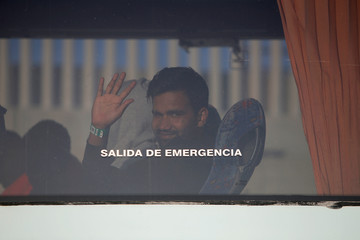 A migrant waves from a bus after arriving on a rescue boat at the port of Tarifa