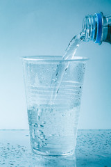 Pure fresh water is pouring into glass or plastic cup in drops close up, healthy drink