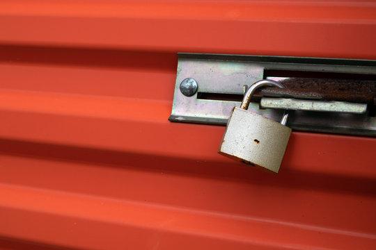 Brass Padlock on Orange Metal Door.