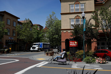 A cyclist on a recumbent bicycle rides through the old downtown area in Windsor, California