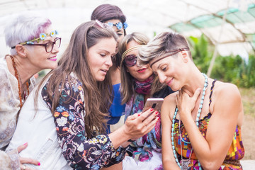 hippy group of caucasian beautiful females looking a smartphone to see a picture or internet results on the web. nice attractive people stay together in happy leisure activity with friendship