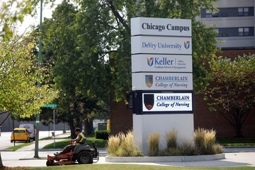 A man rides a lawnmower as he cuts the grass on the campus of DeVry University in Chicago