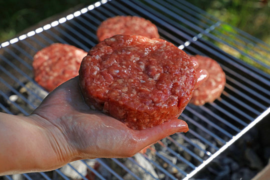 Hand with raw beef burger for hamburger