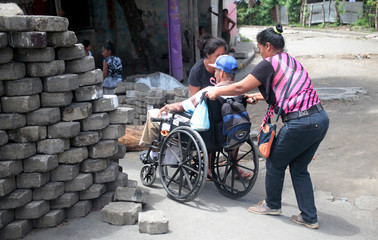A woman pushes the wheelchair of a relative, as they pass a barricade in the indigenous community of Monimbo in Masaya