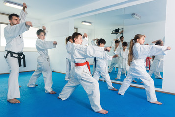Children trying a new moves during karate class