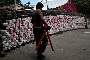 A man carries a makeshift mortar in front of a barricade in the indigenous community of Monimbo in Masaya