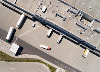 Aerial view of warehouse with trucks. Industrial background. Logistics from above.