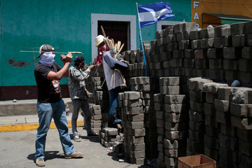 Demonstrators stand behind a barricade in the indigenous community of Monimbo in Masaya