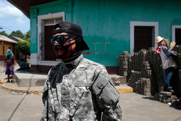 A demonstrator stands behind a barricade in the indigenous community of Monimbo in Masaya