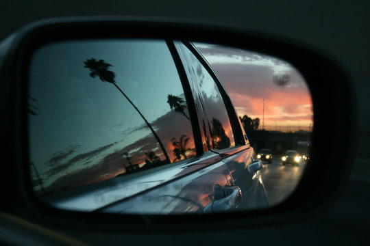 Sunset in Los Angeles seen from the side mirror of a car driving along the road