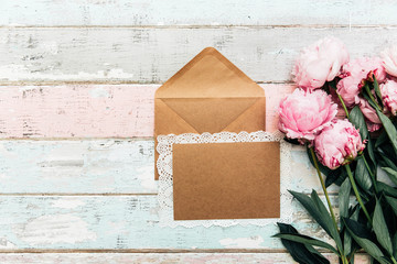 Flat lay empty card invitation with envelope. Festive background with sweet pink peonies flowers .Top view with place for text.