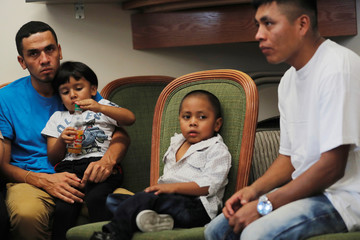 Javier, a 30 year old from Honduras, holds his 4 year old son William and Adan, a 26 year old from Guatemala sits next to his 4 year old son, Juan, during a media availability in New York after they were reunited following being detained and separated