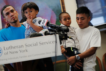 Javier, a 30 year old from Honduras, holds his 4 year old son William and Adan, a 26 yearsold from Guatemala holds his son 4 year old Juan during a media availability in New York after they were reunited following being detained and separated