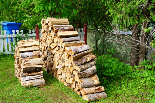 A pile of split logs in the backyard ready for a cold winter in order to heat the house.
