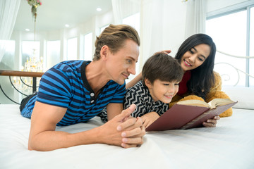 family being playful at home , child at home reading a book for relaxing