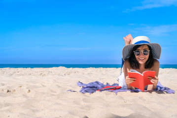 Woman happy smiling and read books on the beach on the beach on a beautiful . Pretty girl asian in casual looking away and smile , laughing. The beach beautiful at bright sky Wall mural