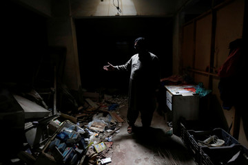 Zakir Hanif, an activist of Awami National Party, stands at his pharmacy store which was bombed by Tehreek-e-Taliban Pakistan, in Karachi