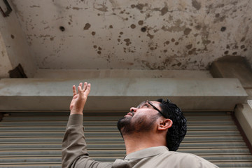 Zakir Hanif, an activist of Awami National Party, points to the ceiling of his pharmacy store which was bombed by the Tehreek-e-Taliban Pakistan, in Karachi