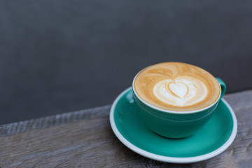 Beautifiul cup of hot cappuccino on the wood background. Heart shape latte art. Side-view, copy space for your text.