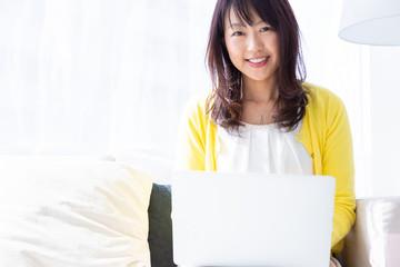 部屋でパソコンを見るミドル女性