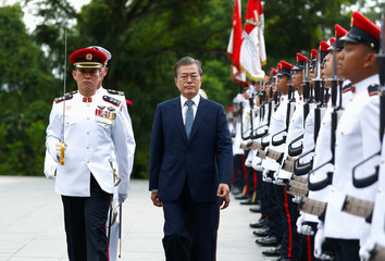 South Korea's President Moon Jae-in inspects an honor guard with Singapore's President Halimah Yacob during a visit at the Istana in Singapore