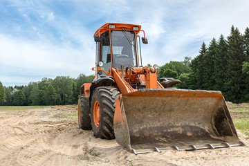 wheel loader with backhoe standing outdoors. construction machinery