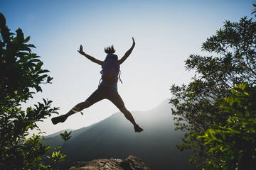 successful hiker jumping on summer sunrise mountain top cliff edge